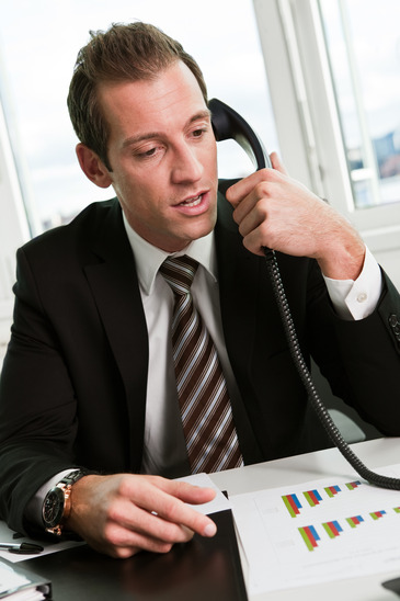 Young businessman speaking on the phone at workplace